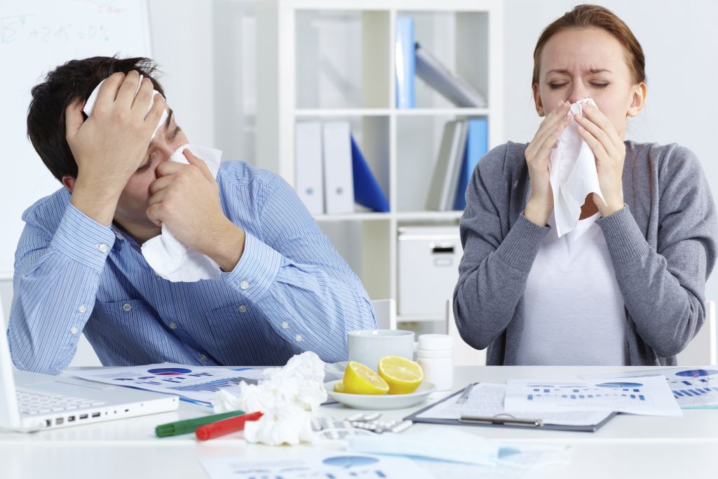 Image of sick business partners blowing their noses in office