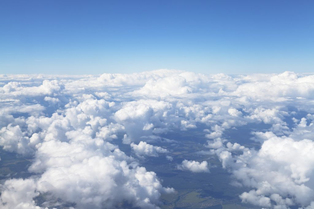 View of white clouds in blue sky and lands under clouds